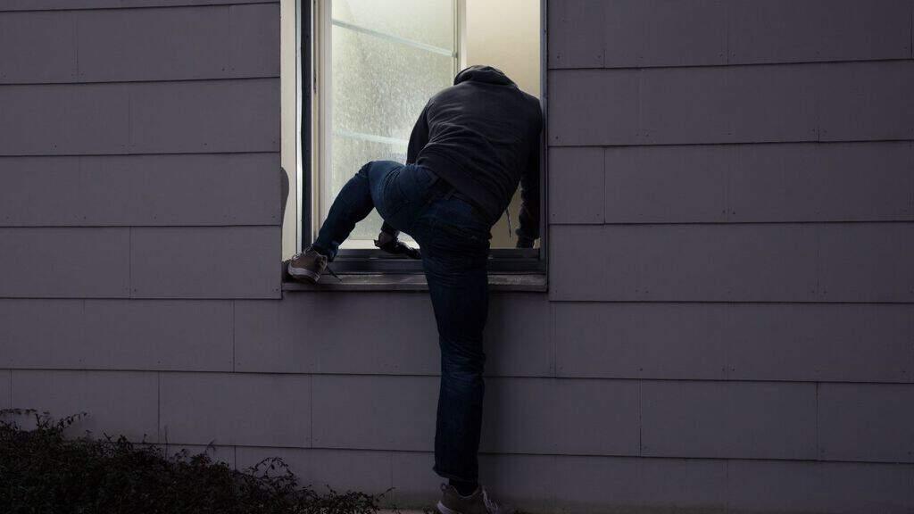ladro di spalle che cerca di entrare da una finestra