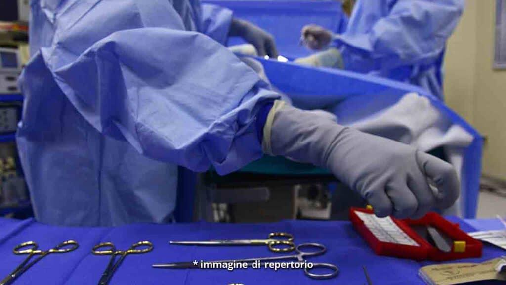 Mano di chirurgo che prende bisturi