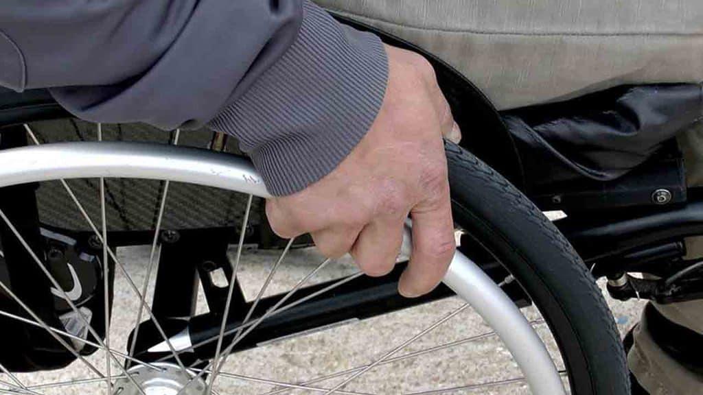 mano di uomo su sedia a rotelle