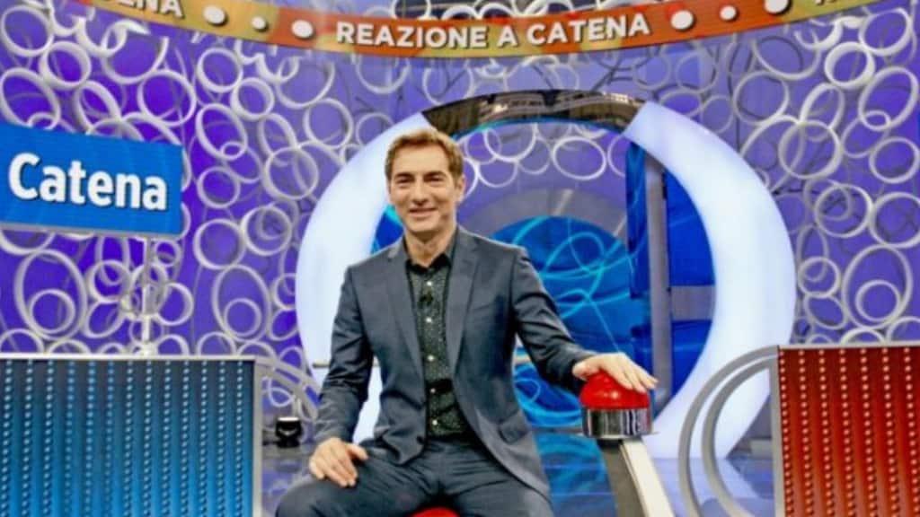 """Il conduttore Marco Liorni seduto nello studio di """"Reazione a Catena"""""""