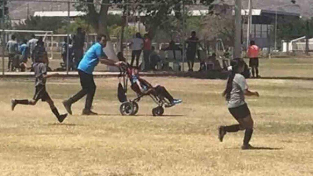 Padre e figlio disabile giocano a calcio con i bambini