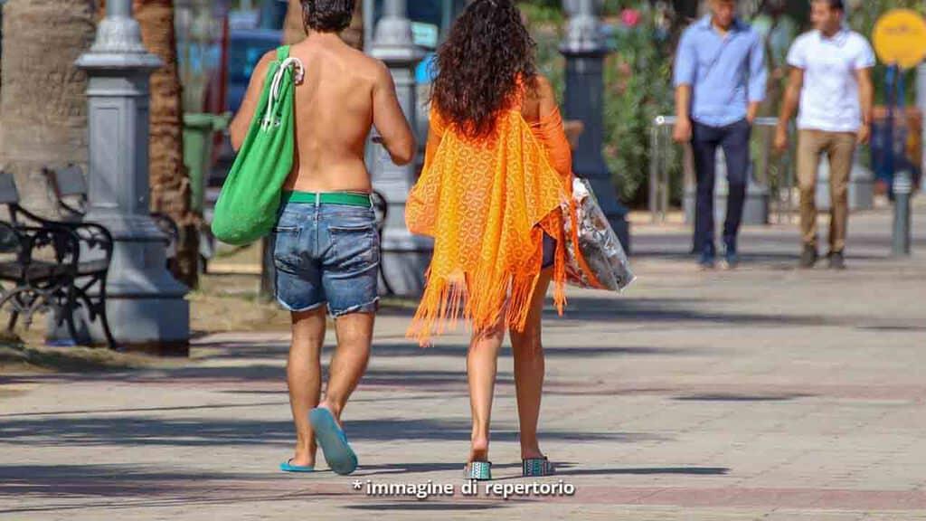 Coppia di spalle che passeggia in città tra la gente