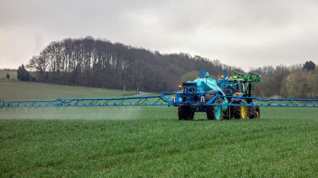 Un trattore nei campi mentre spruzza i pesticidi