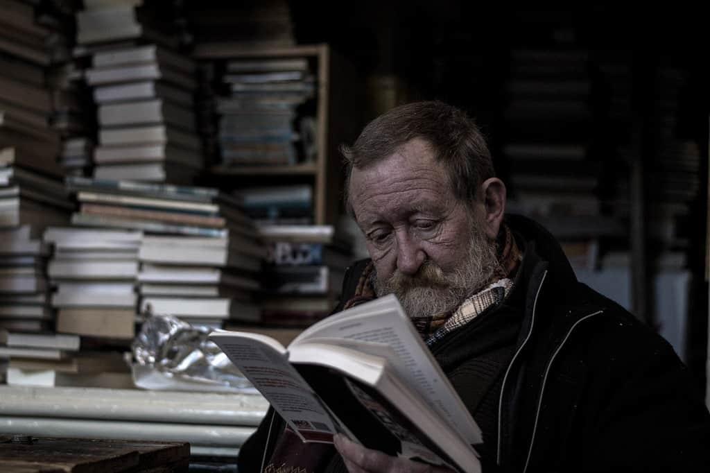 Un uomo anziano legge un libro in solitudine.
