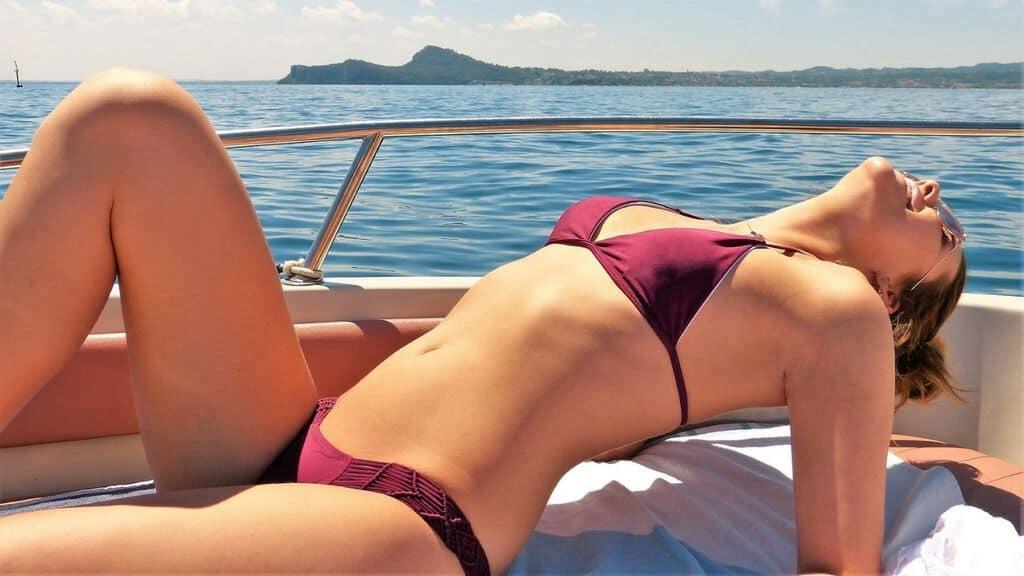 una donna che si abbronza sulla barca in mare