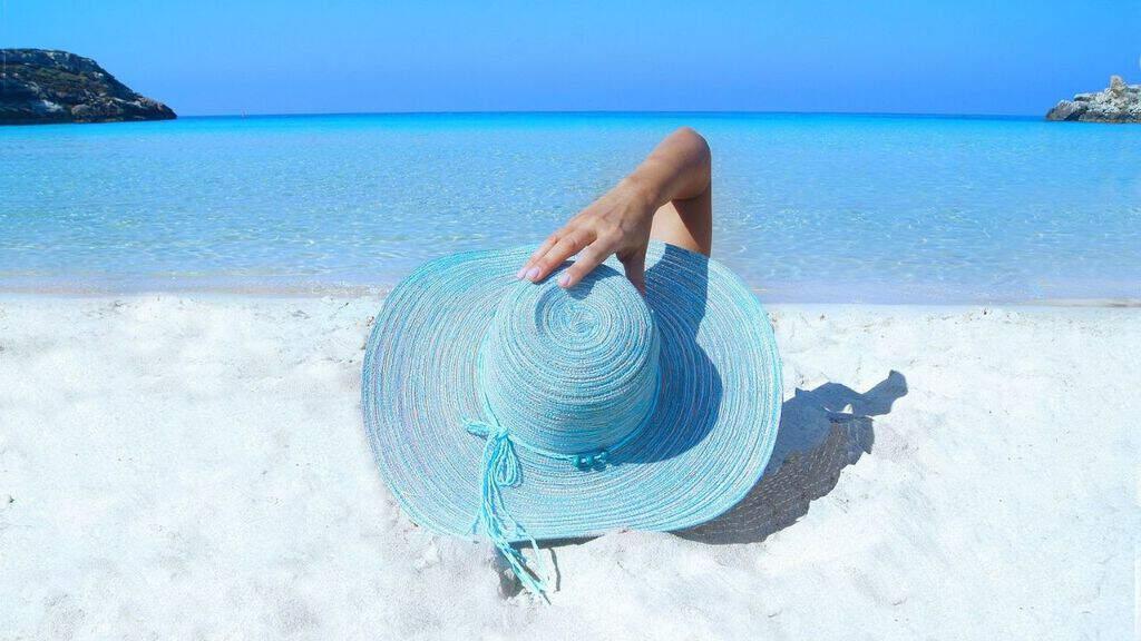 donna sdraiata al mare di spalle con un cappello azzurro