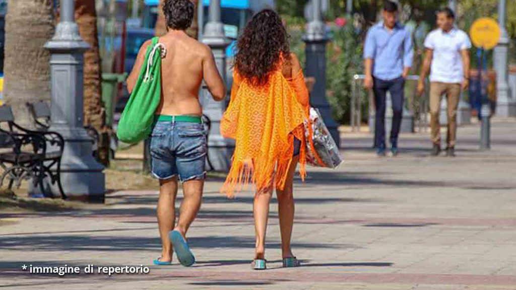 coppia che cammina per strada tra la gente