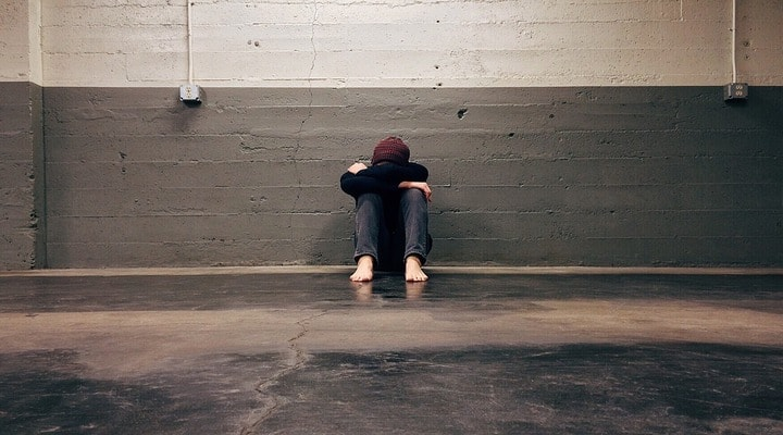 bambino seduto in una stanza, si copre il volto con le braccia
