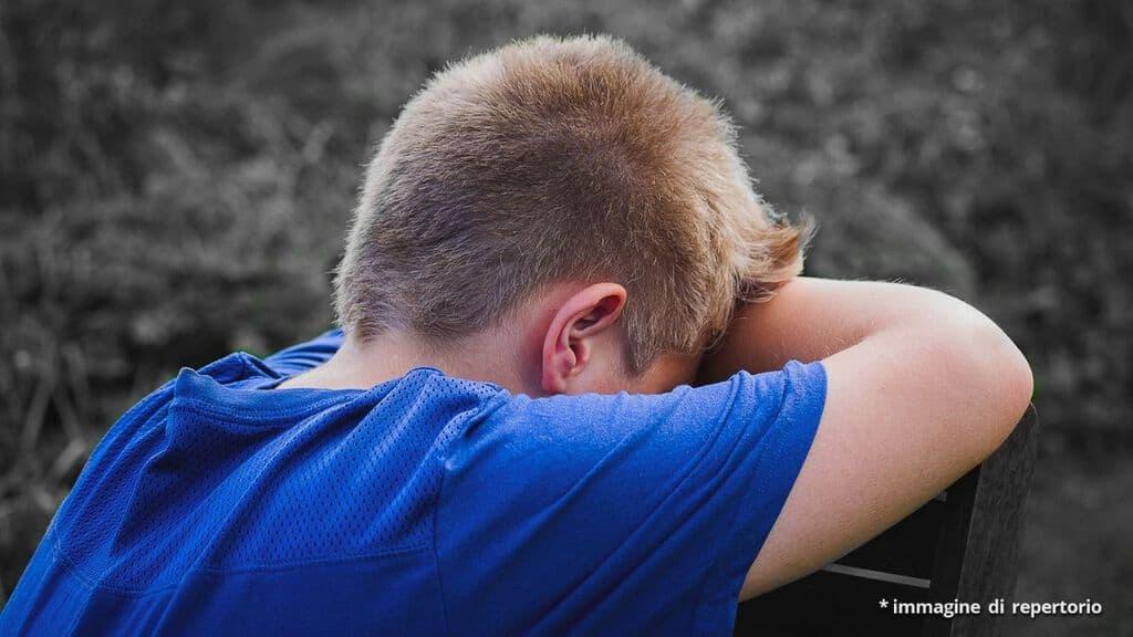 ragazzino che piange seduto su una sedia di spalle