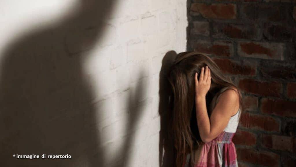bambina con la faccia rivolta verso il muro e le mani sulle orecchie in segno di disperazione