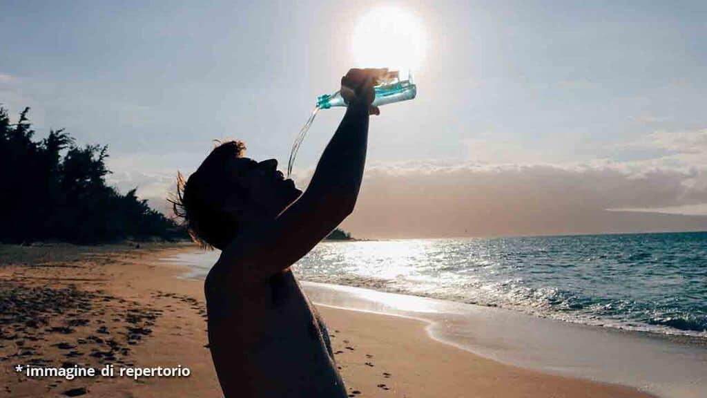uomo beve in spiaggia