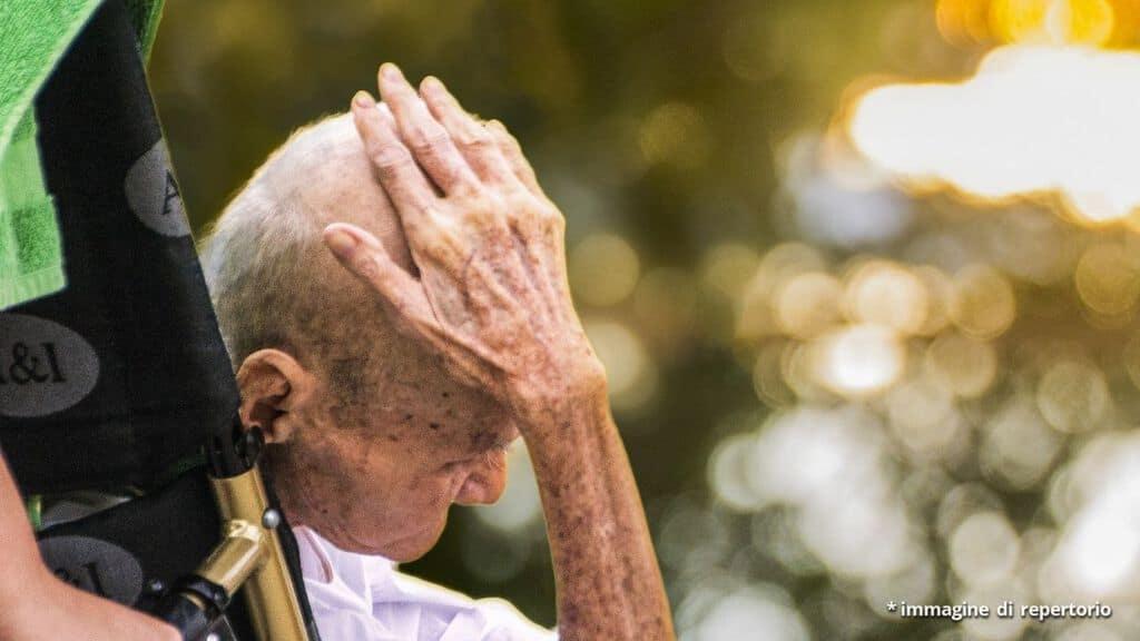 anziano in sedia a rotelle di spalle con una mano sulla testa