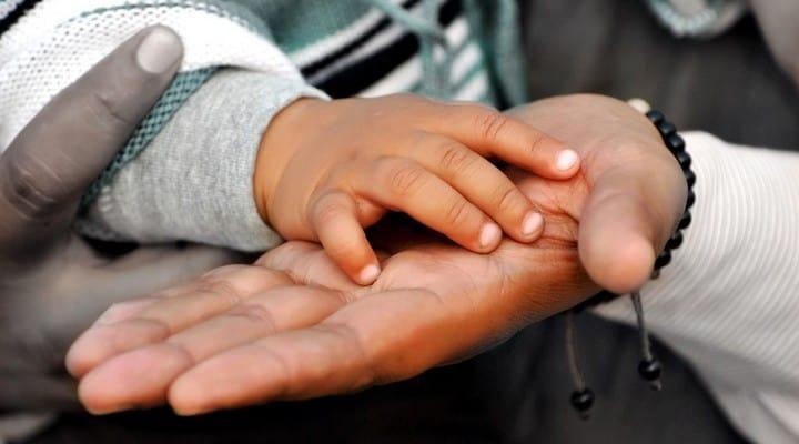 mano di bimbo nella mano di un adulto