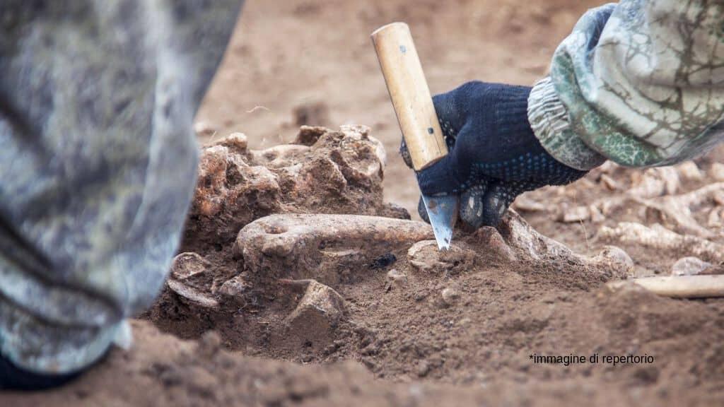 uomo scava vicino ossa nella terra