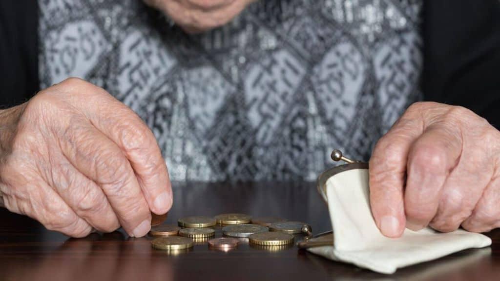 mani di anziana con dei soldi sul tavolo