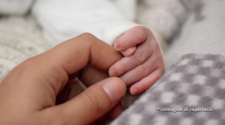mano di donna e neonato