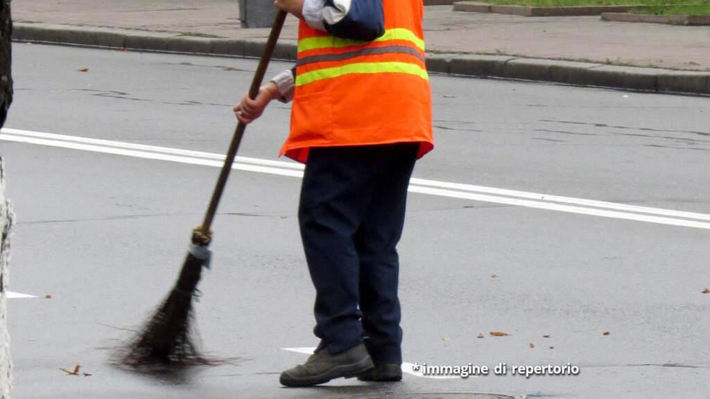 uomo che raccoglie foglie per strada