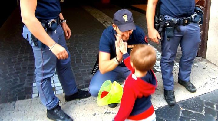 Bimbo consegna fiore ai poliziotti