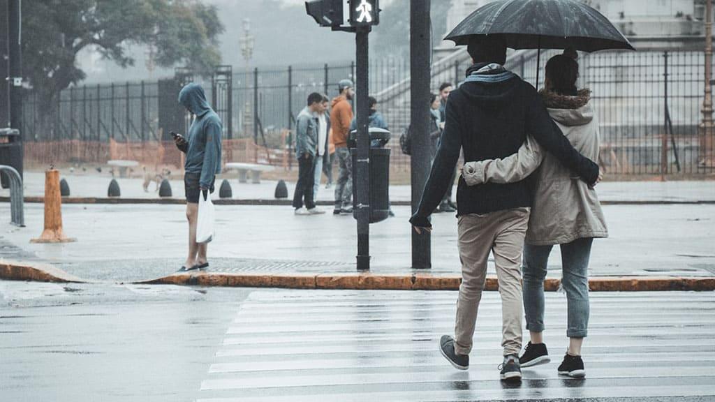 coppia sotto la pioggia tra la gente