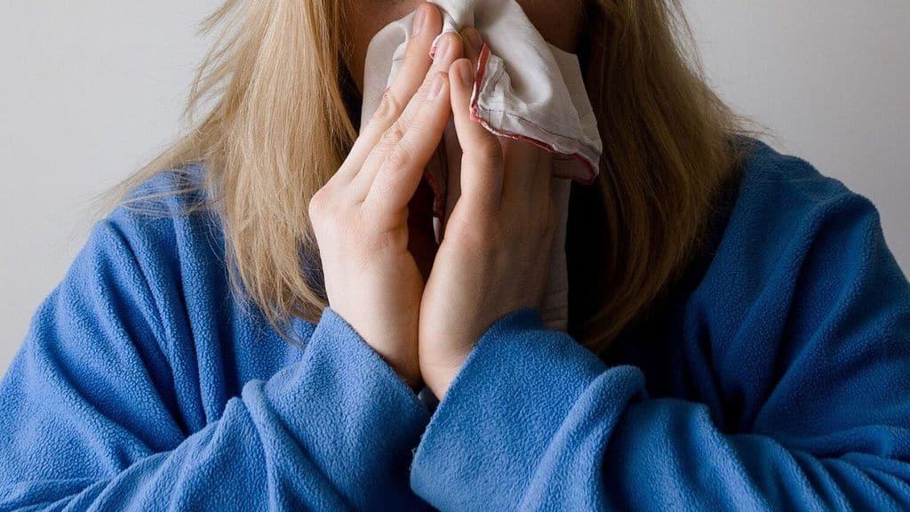 donna mentre si asciuga il naso con un fazzoletto