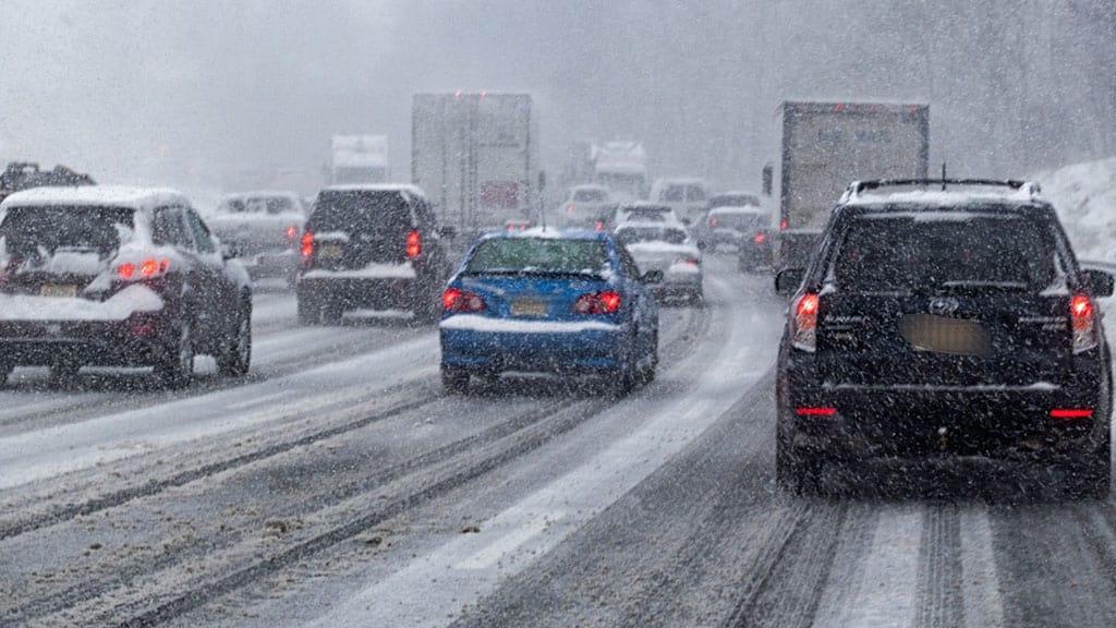 macchine su strada sotto la neve