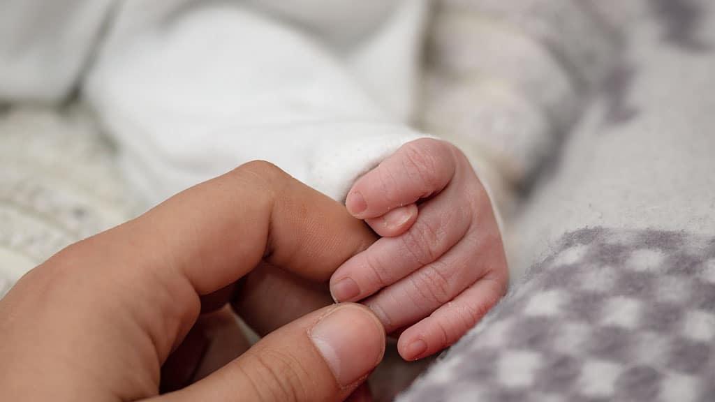 mano di uomo e neonato