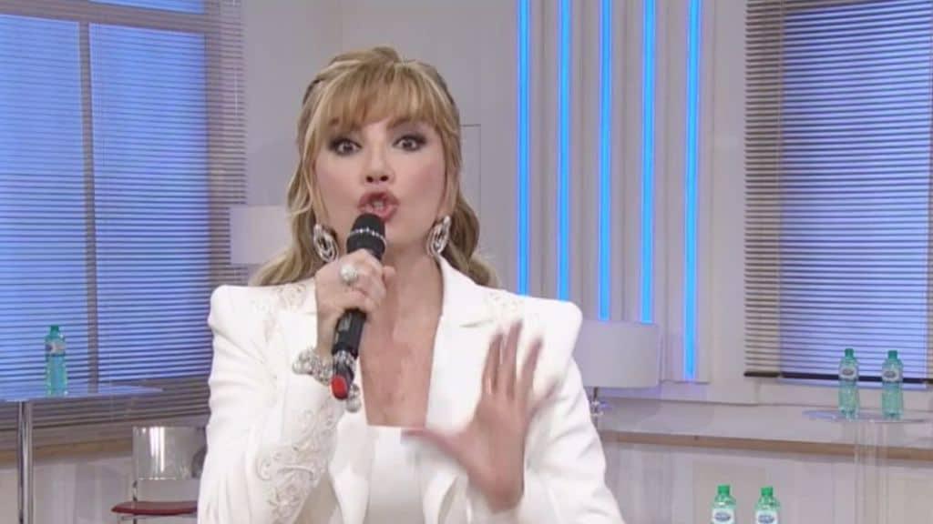 milly carlucci con un microfono in mano