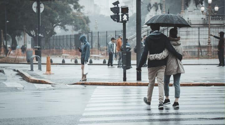Persone sotto la pioggia con ombrello