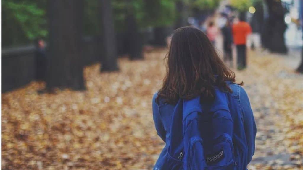Bambina che cammina con lo zaino in spalla