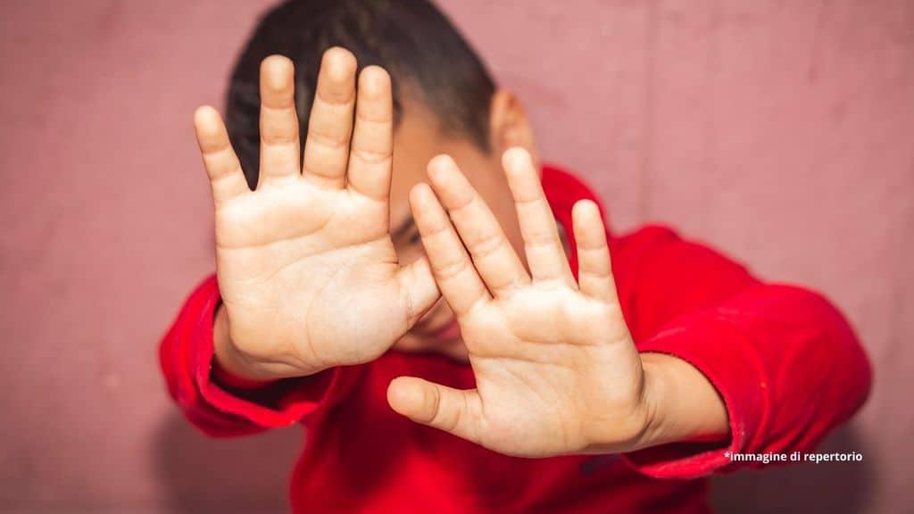 bambino che si copre il volto con le mani