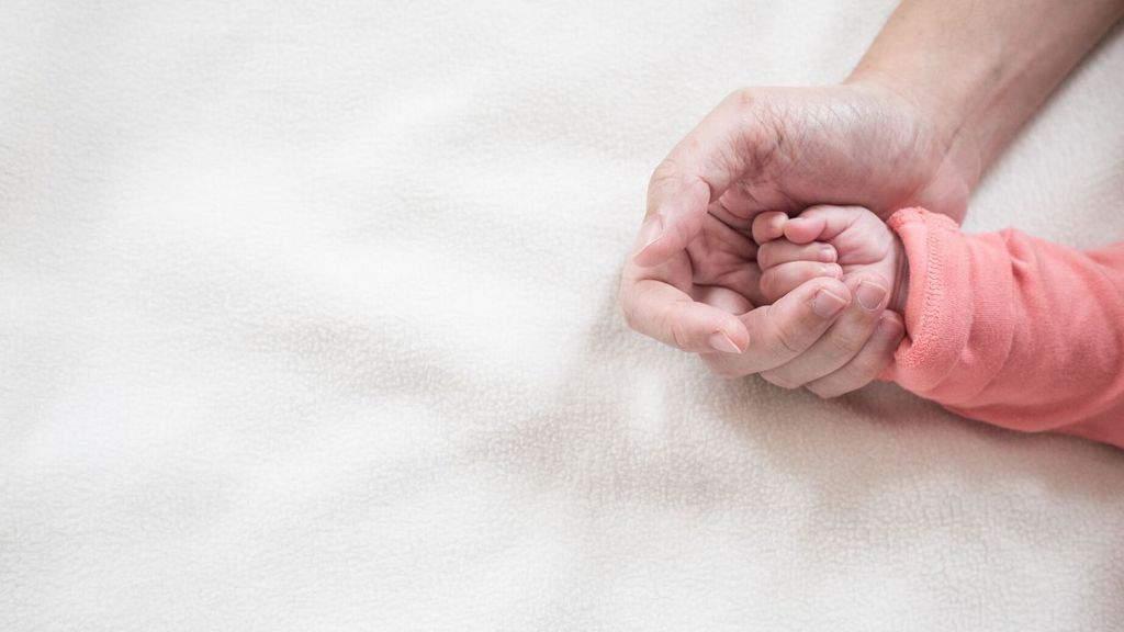 mano di una neonata in quella della mamma