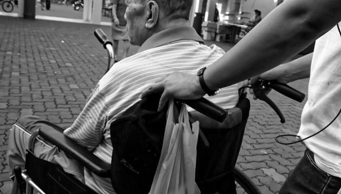 badante che spinge un anziano in carrozzina