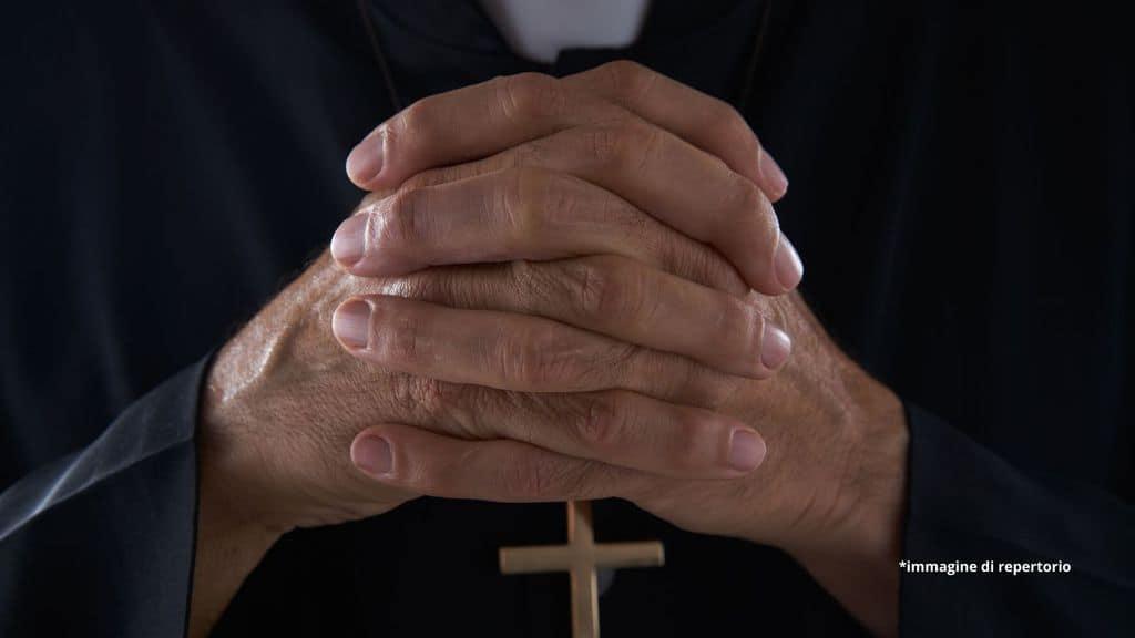 mani di un prete giunte