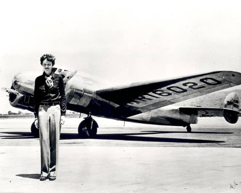 amelia earhart in piedi di fronte al suo aereo