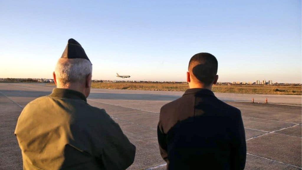Di Maio di spalle mentre guarda atterrare l'aereo militare con Niccolò