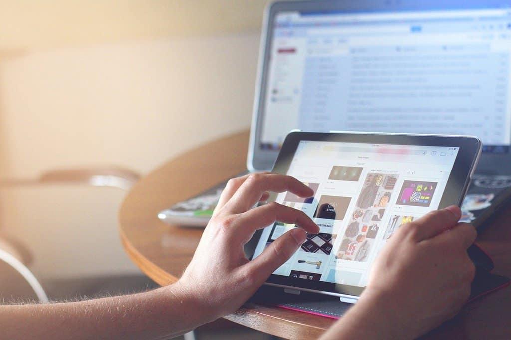 mani di donna che tengono un tablet, sullo sfondo lo schermo di un computer