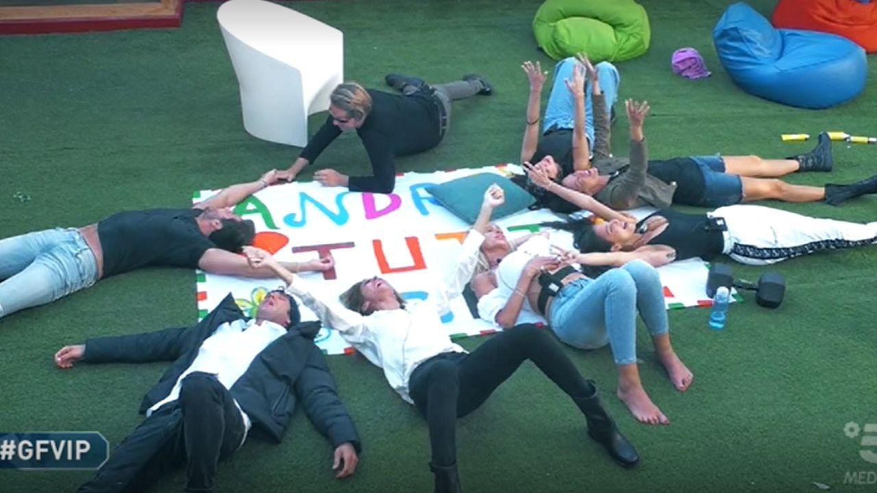 I concorrenti del GF Vip sdraiati in cerchio sul cartellone con la scritta