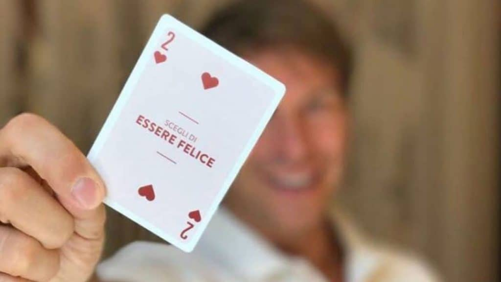 Walter Rolfo con una carta in mano con scritto Essere Felici