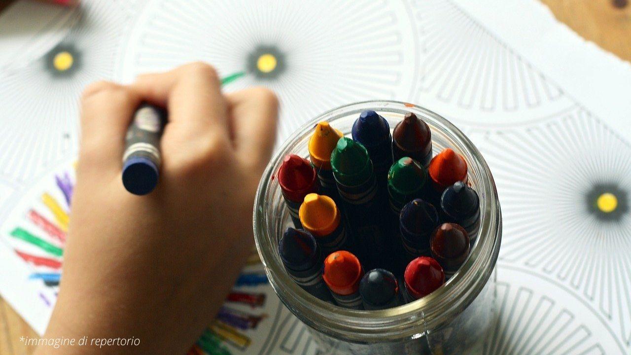 Mano di un bambino che colora con i pastelli