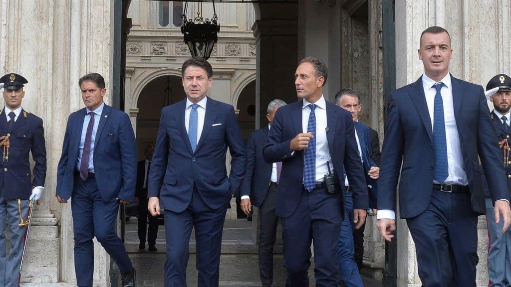 Giuseppe Conte che cammina in strada con la scorta