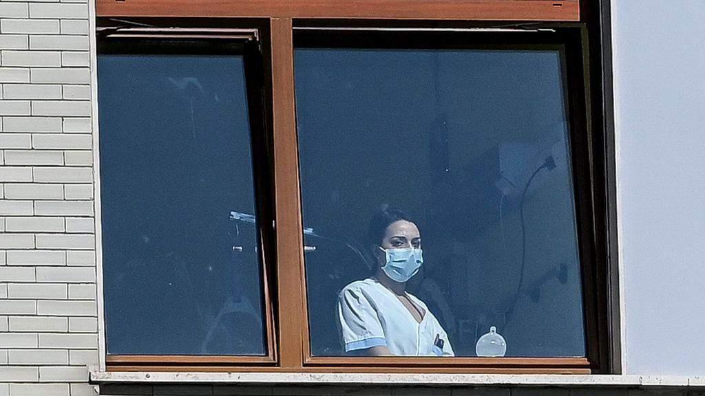 infermiera con la mascherina alla finestra