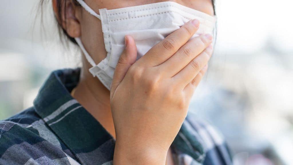 una donna che si tiene la mascherina