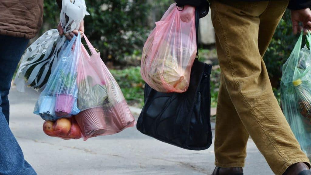 persone con in mano sacchetti di plastica