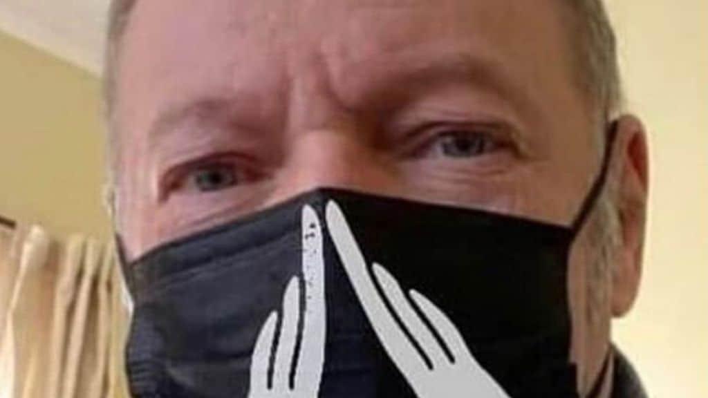 Vasco Rossi in primo piano con una mascherina nera addossocon la mascherina