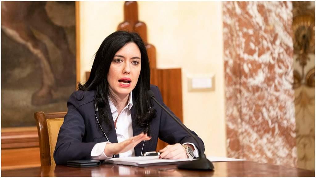 Lucia Azzolina seduta alla scrivania con davanti dei fogli mentre tiene una mano tesa come ad invitare alla calma