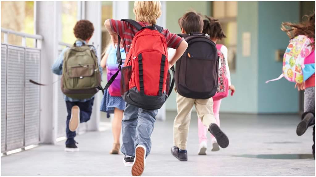 bambini con lo zaino di spalle che corrono verso la scuola