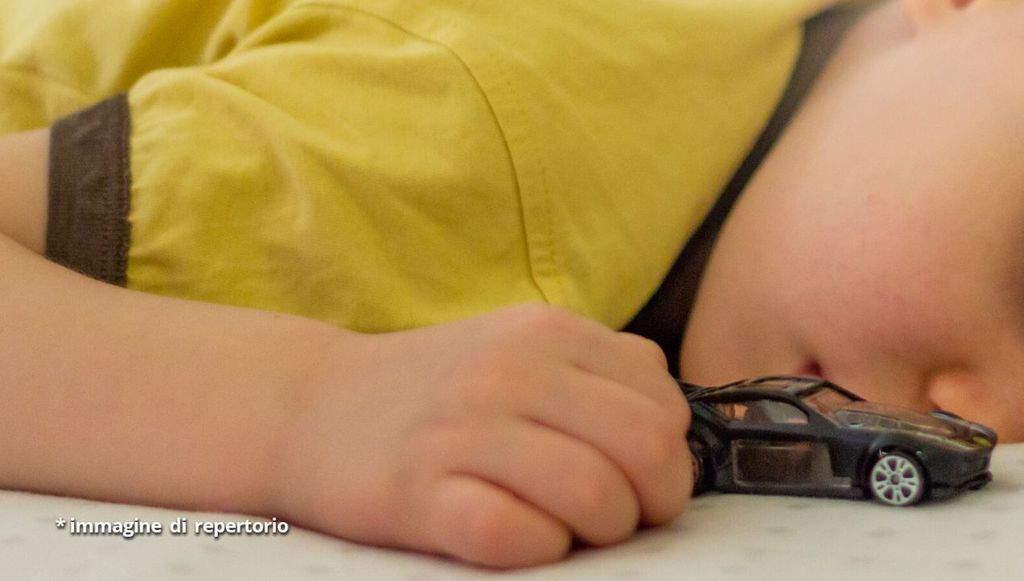 bambino che dorme con in mano una macchinina
