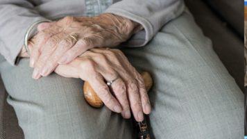 mani di donna anziana appoggiate sulle gambe con un pantalone grigio