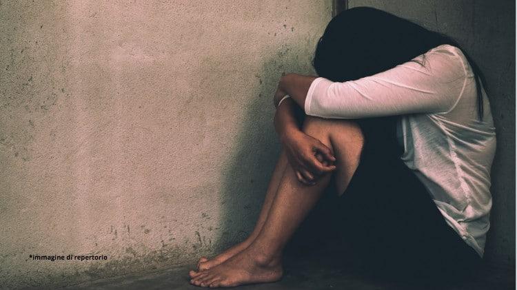 donna vittima di violenza per terra in un angolo