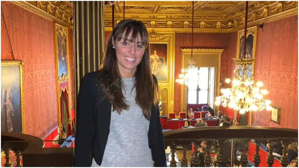 Federica Scanderebech sorridente e in piedi, alle sue spalle la Sala Rossa di Torino